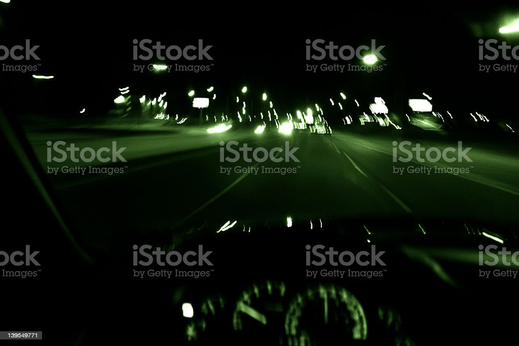 Motion blurred drivers view of a highway with green accents stock photo