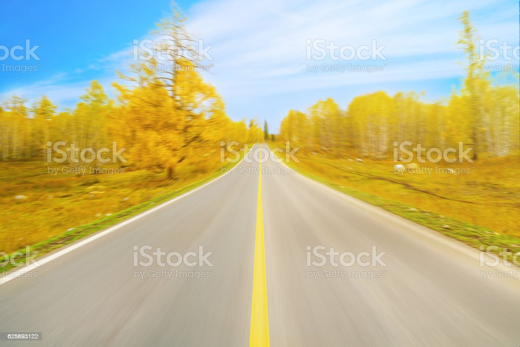 Motion Blurred Empty straight road in the fall stock photo