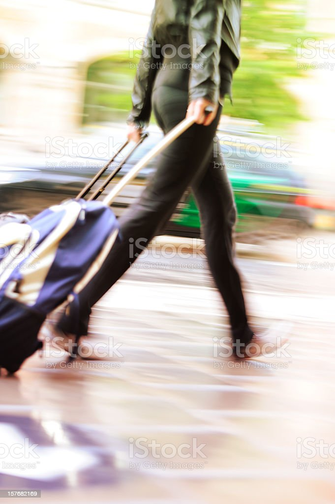 Motion blurred pedestrian with bags on sidewalk in rain royalty-free stock photo