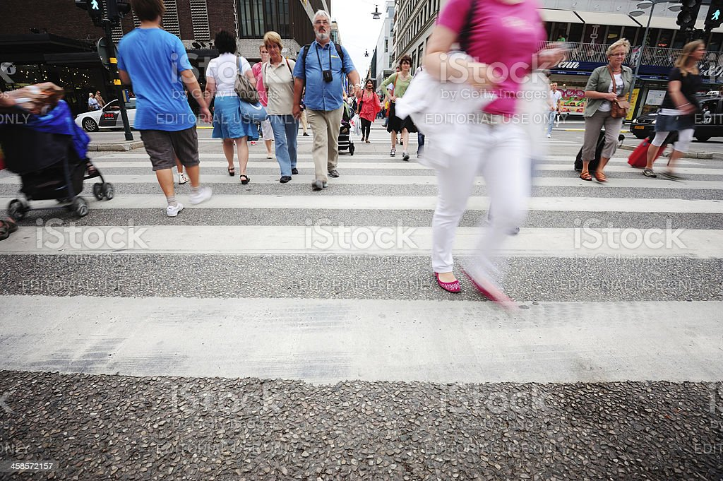 Motion blurred pedestrians crossing street royalty-free stock photo