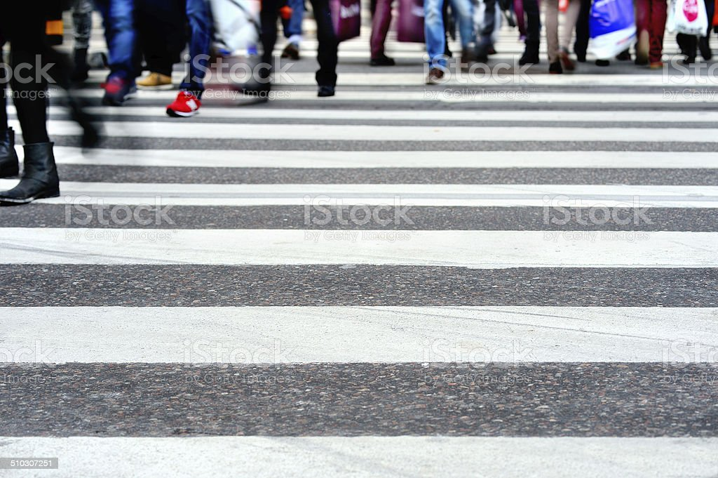 Motion blurred pedestrians crossing sunlit street stock photo