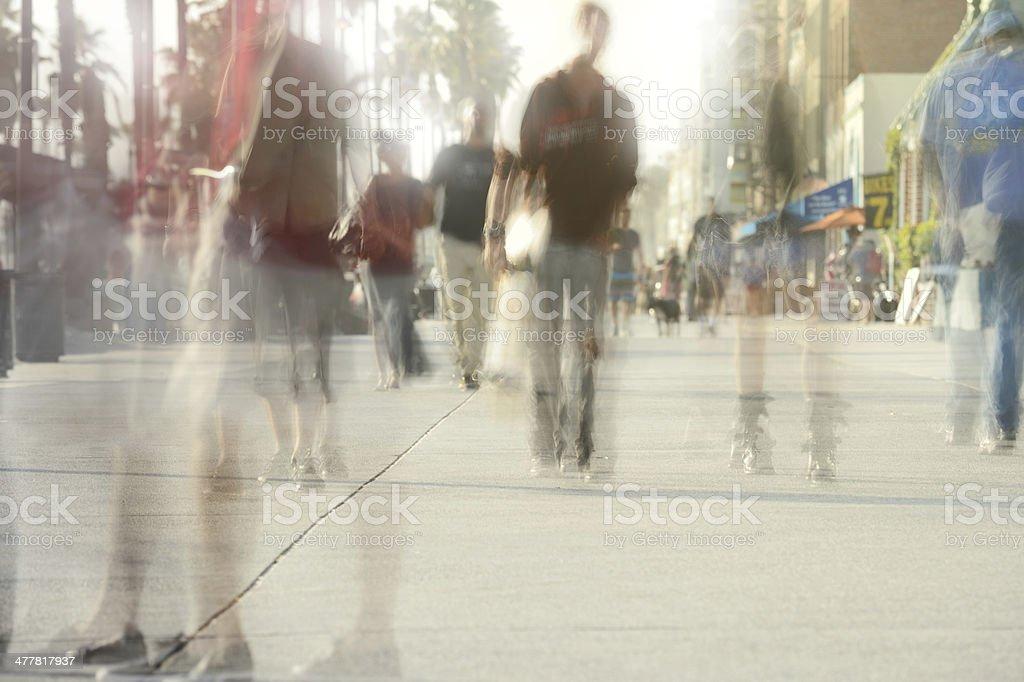 Motion blurred pedestrians on boardwalk royalty-free stock photo