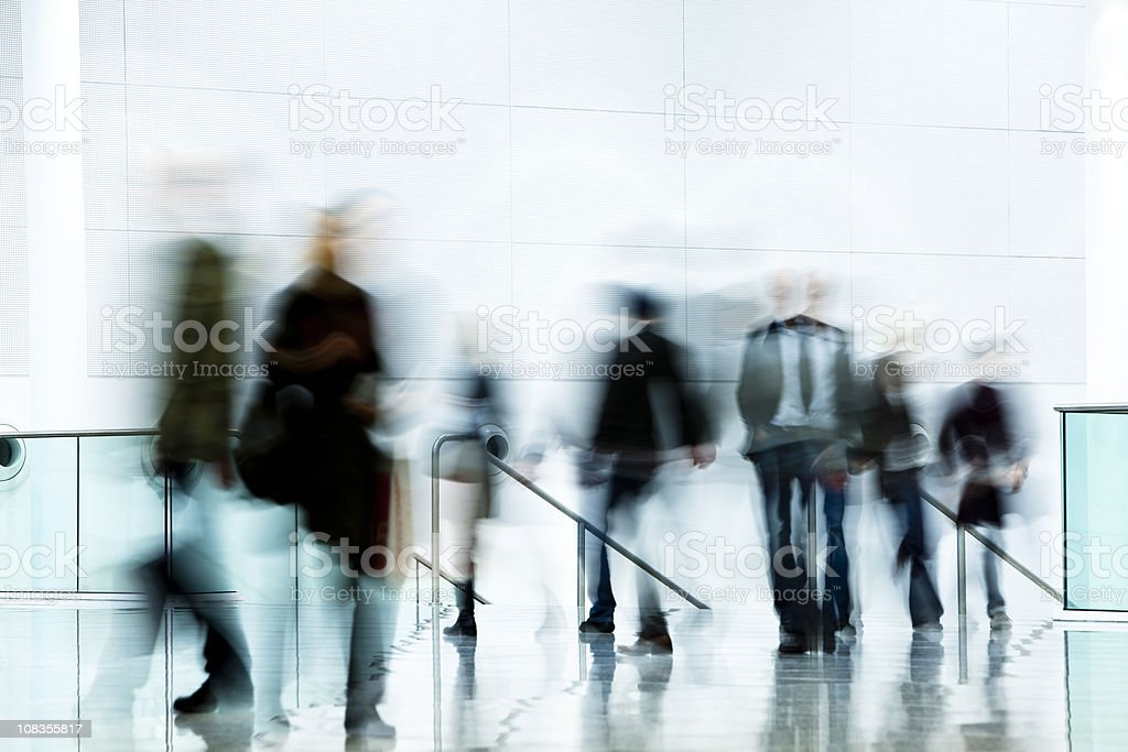 Motion Blurred Pedestrians Walking in White Hallway royalty-free stock photo