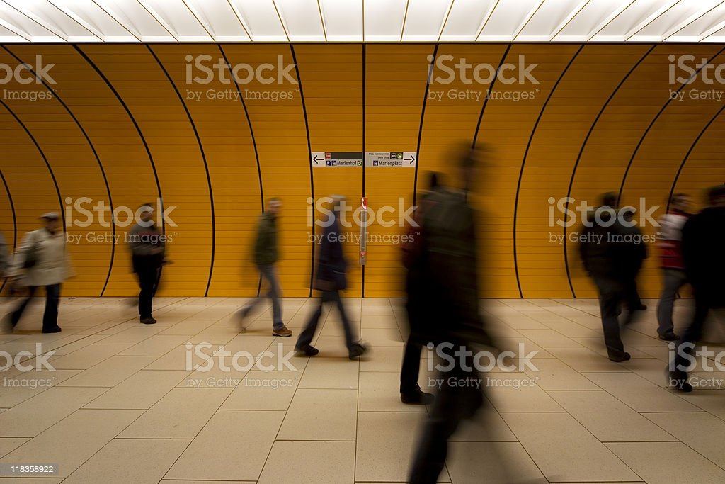 motion blurred people against modern orange tunnel royalty-free stock photo