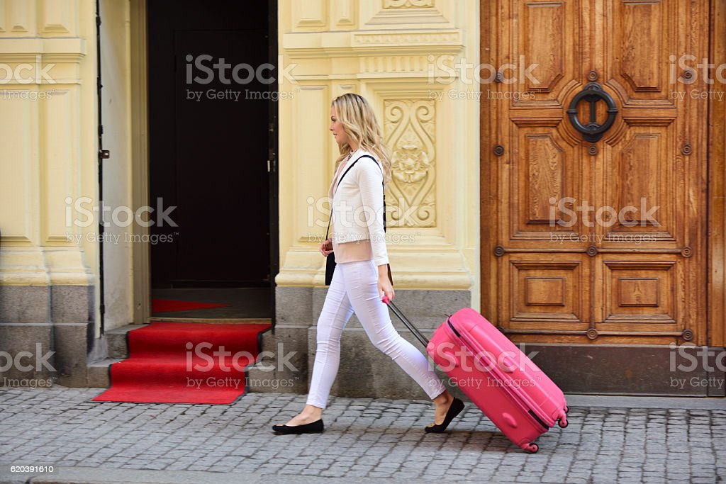 Motion blurred stylish woman with bag walking on street stock photo