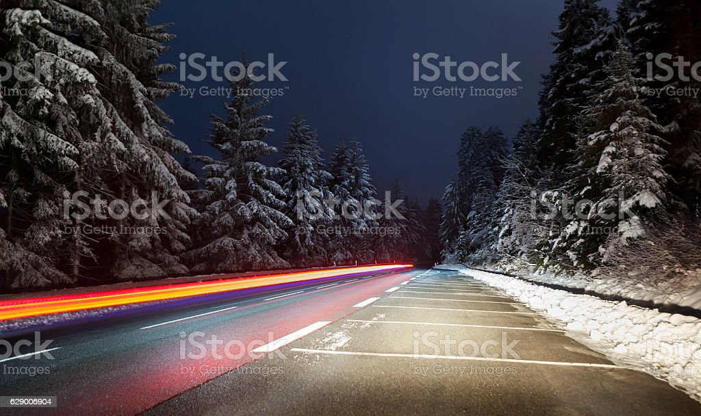 Motion blurred tail light winter forest stock photo