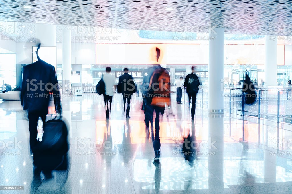 motion blurred travellers walking in modern airport hallway stock photo