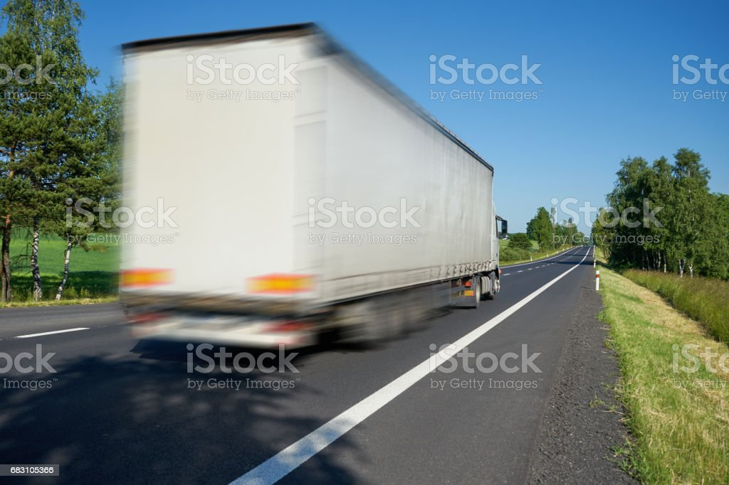 Motion blurred white truck driving on the road a landscape stock photo