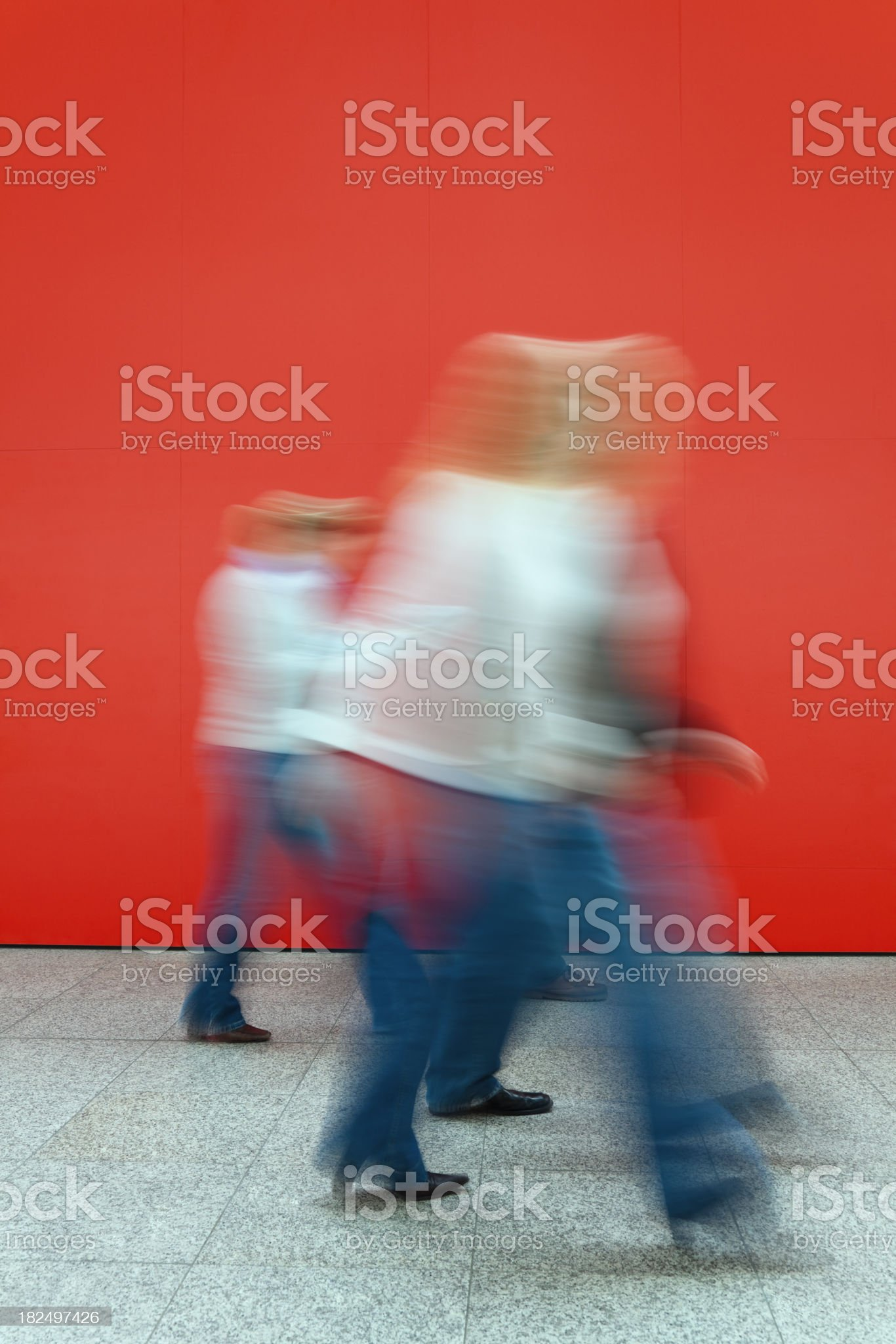 Motion Blurred Women Walking Against a Red Wall royalty-free stock photo