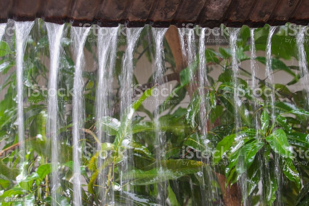 Motion drop of water rain from roof at night stock photo
