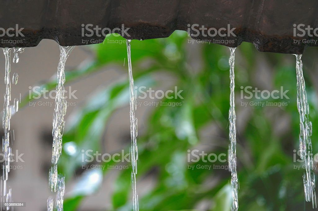 Motion  drops of water rain  from roof,  soft focus water stock photo