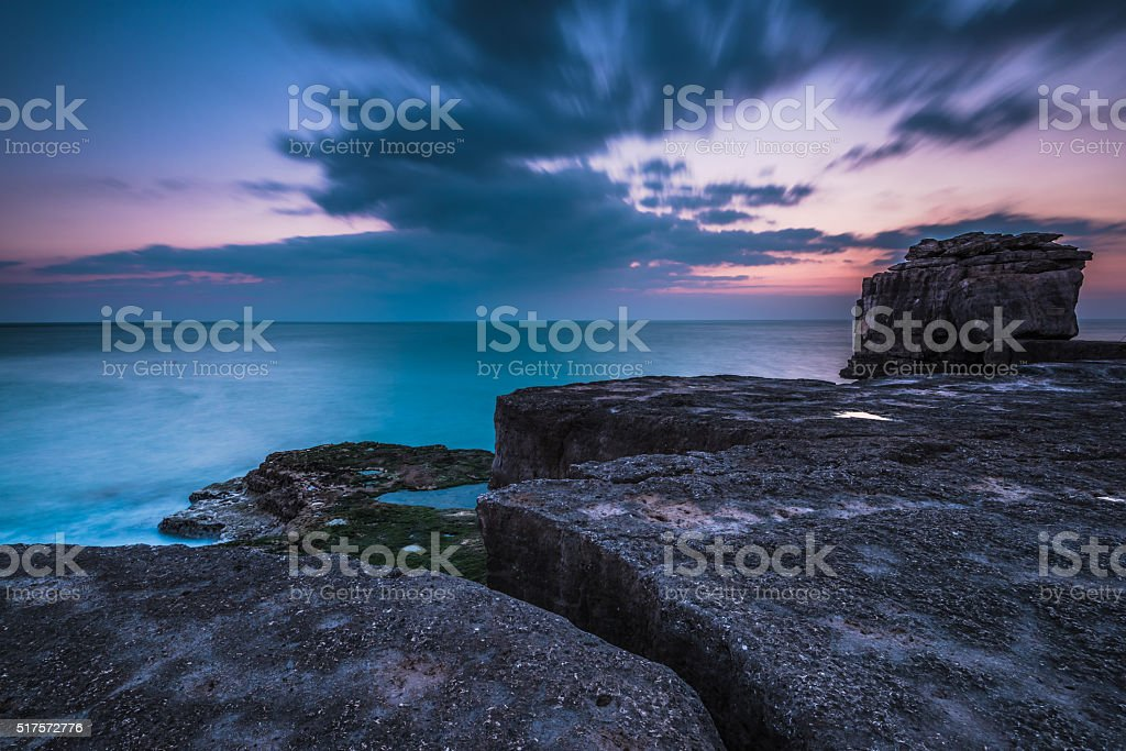 Motion moving clound at sunset at rocky cliffs stock photo
