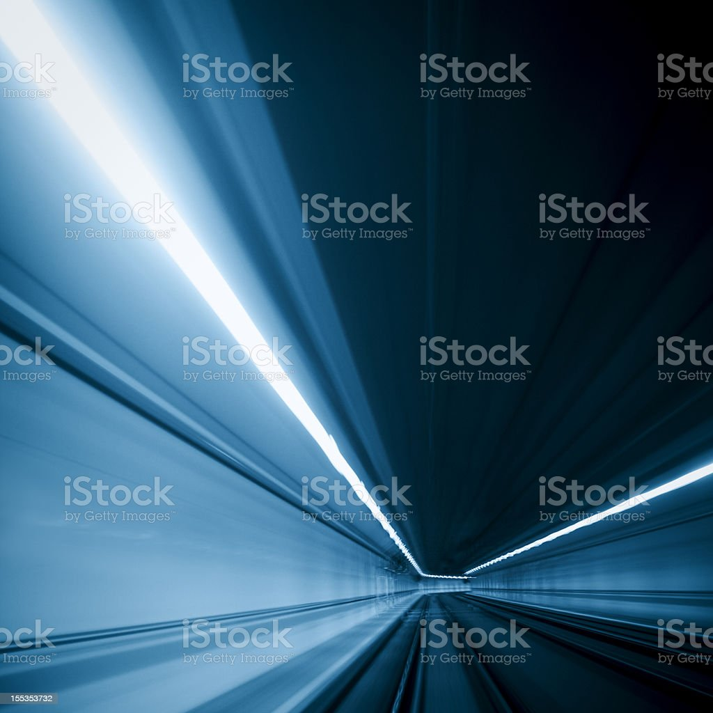 Motion photo of blue light traveling through a tunnel stock photo