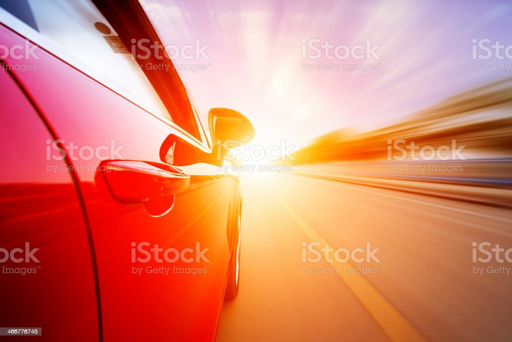Motion photograph of a red car driving into the sun stock photo