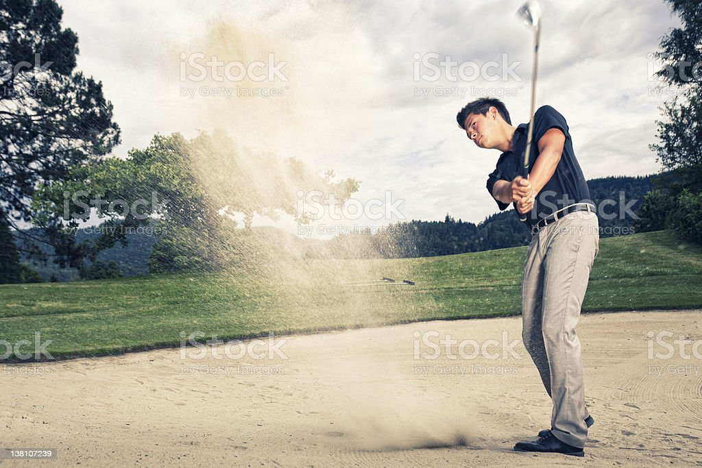 Motion shot of golf player in sand trap stock photo