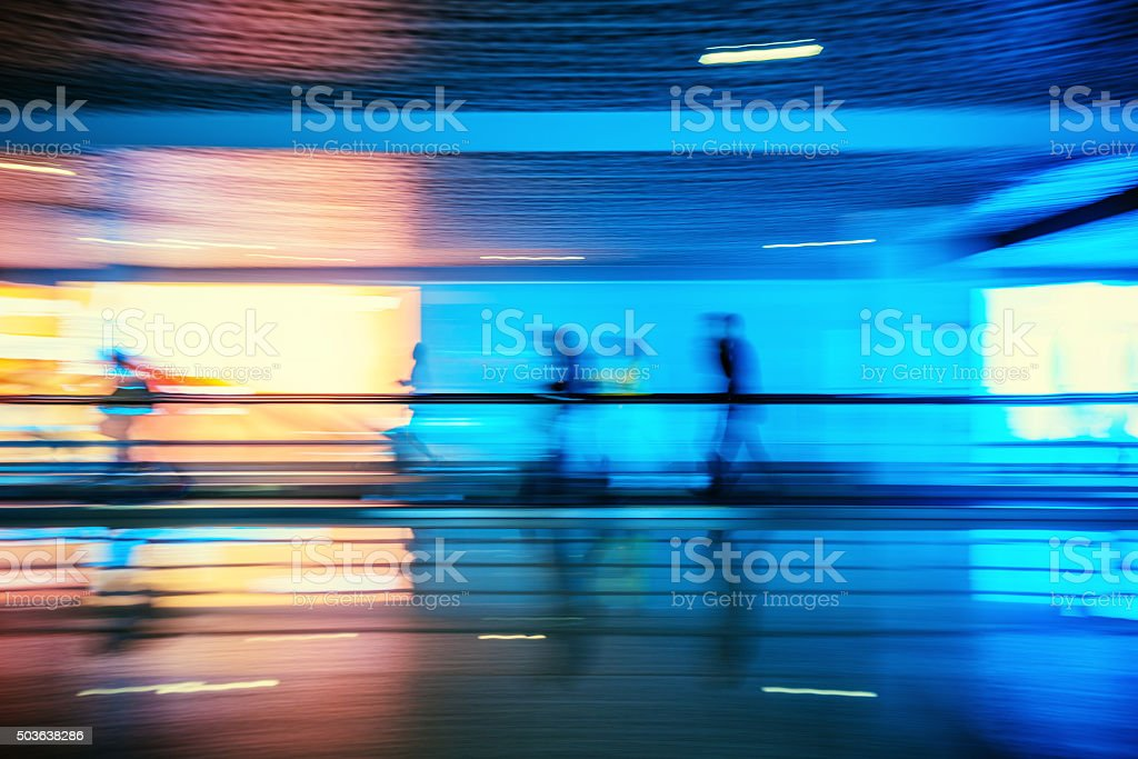Motion-blurred abstract people walking to the airport terminal stock photo