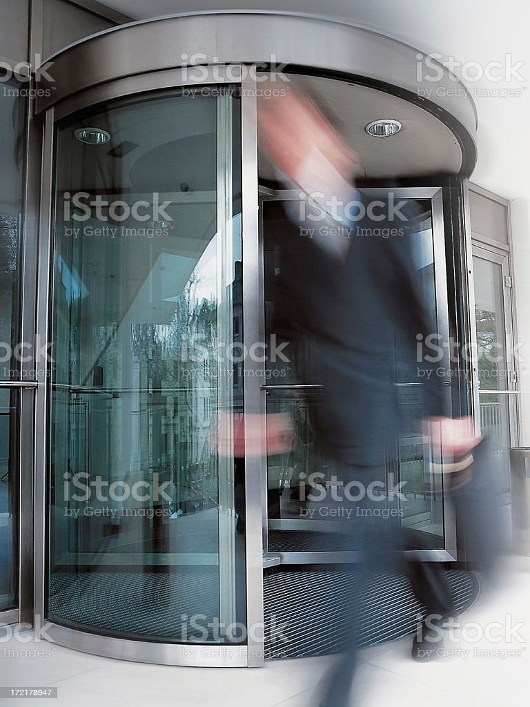 Motion-blurred businessman exiting building's rotating doors royalty-free stock photo