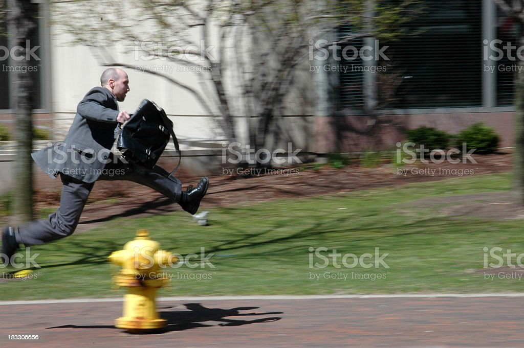 Motion-blurred man running on sidewalk on way to work royalty-free stock photo
