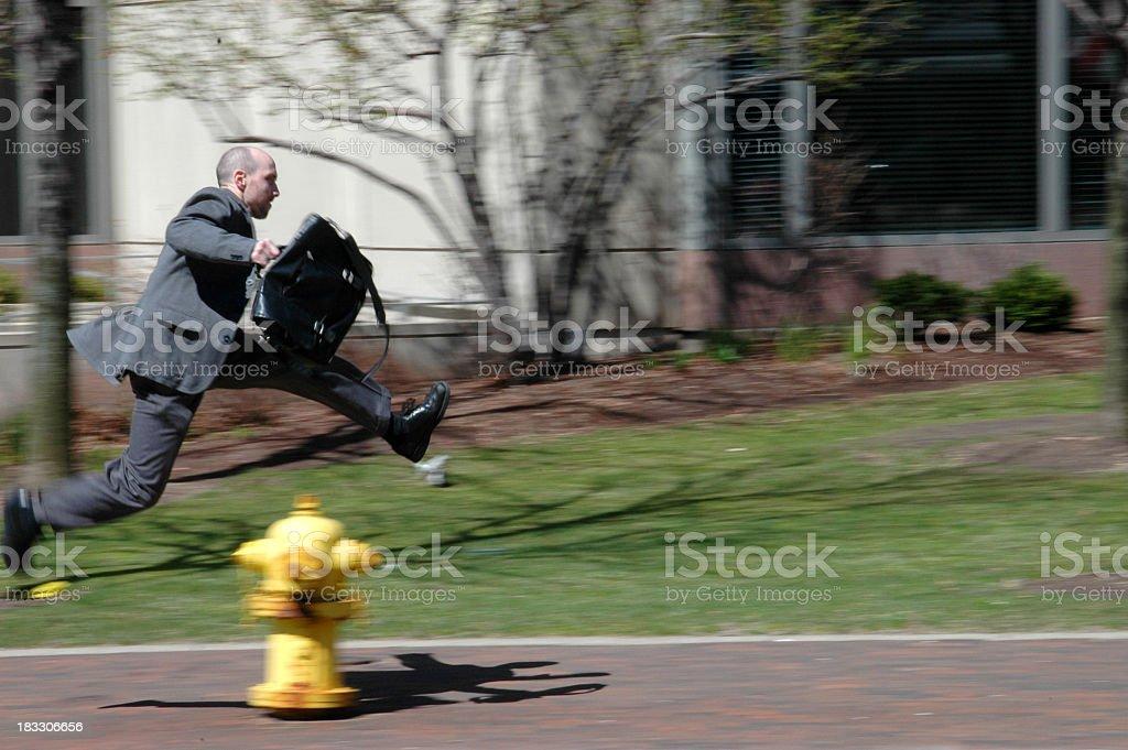 Motion-blurred man running on sidewalk on way to work stock photo