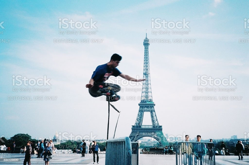 Motion-blurred roller skater jumping near Eiffel Tower, Paris, France stock photo