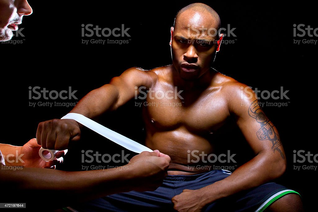 Motivated Black Fighter Preparing with Athletic Tape stock photo