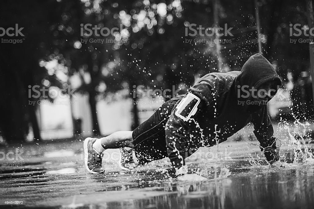 motivated man working out in the rain stock photo