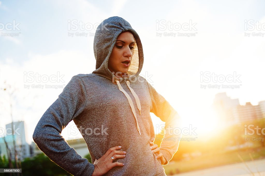 Young athlete stretches in summer sunset in Osaka, Japan, dressed in...