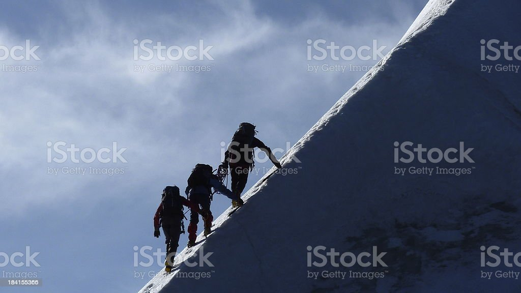 Motivation, Teamwork, Leadership - Mountaineers on a steep mountain ridge stock photo
