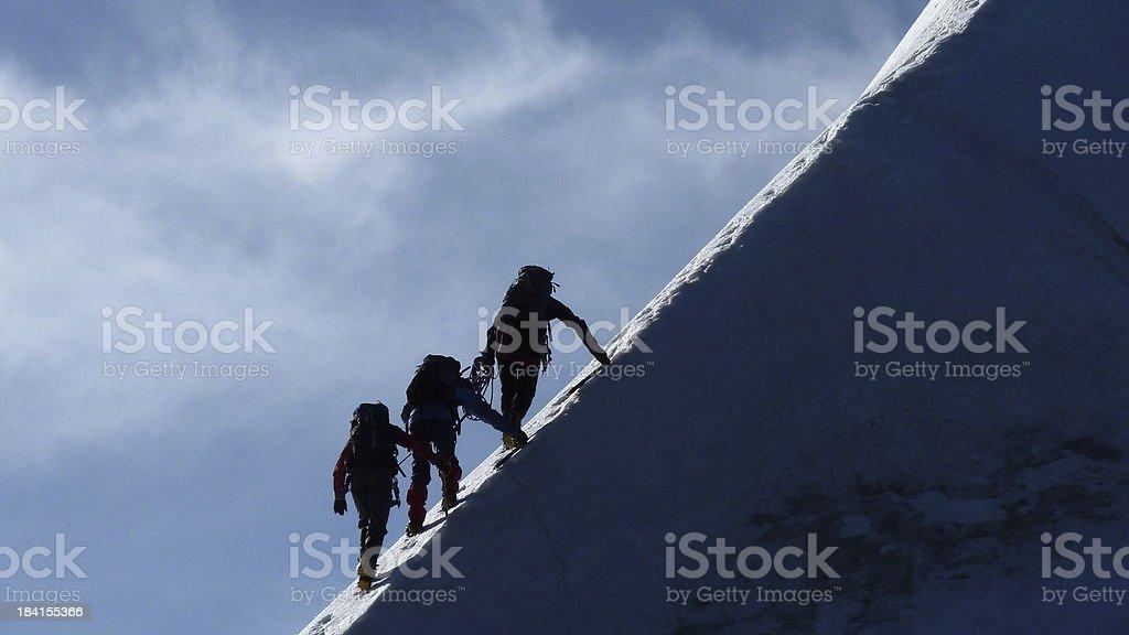 Motivation, Teamwork, Leadership - Mountaineers on a steep mountain ridge stock photo