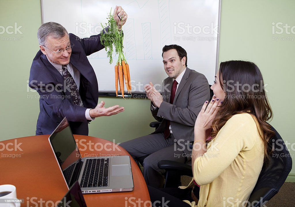 Motivational businessman holding carrots in front of people stock photo