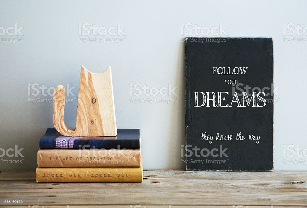 motivational quote  FOLLOW YOUR DREAMS on chalkboard with books stock photo