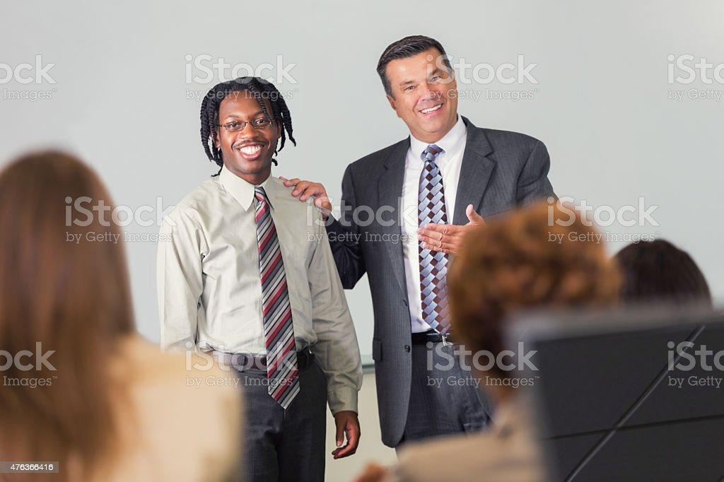Motivational speaker using volunteer during speech or presentation at conference stock photo