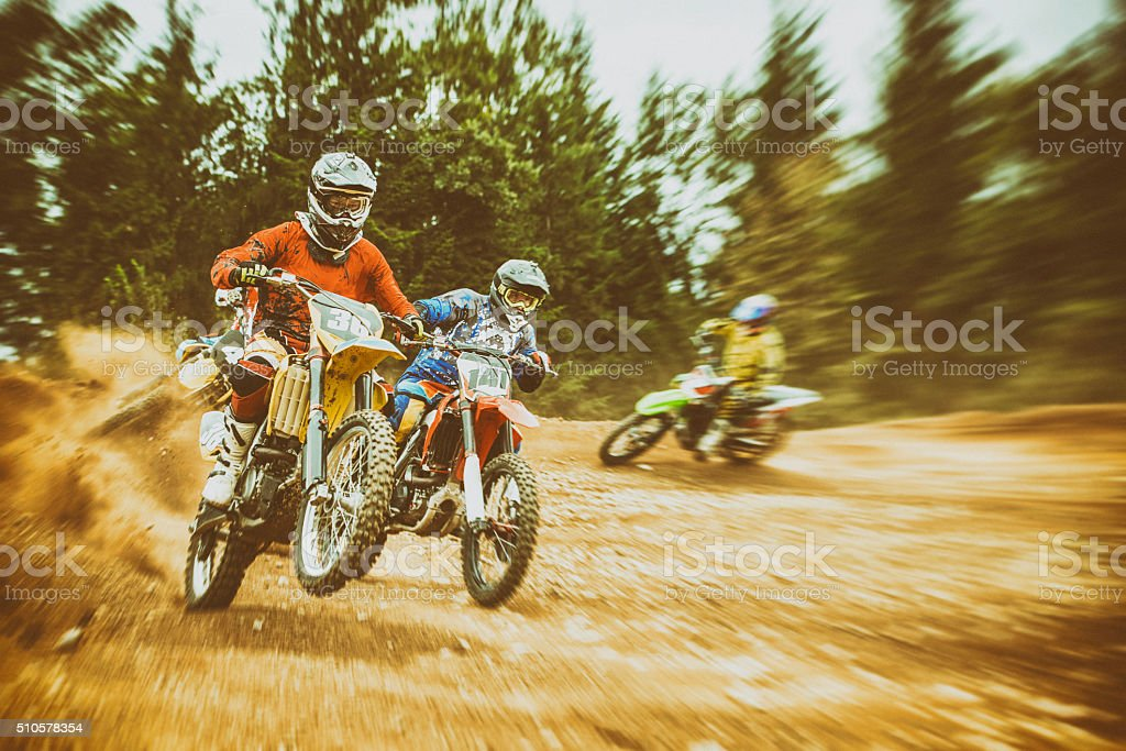 Motocross bikers on a dirt road stock photo