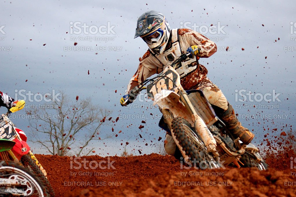 Motocross driver slings mud in the curve stock photo