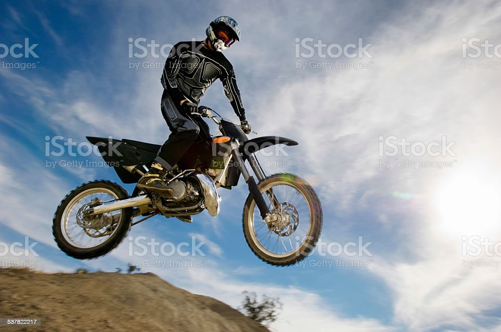 Motocross Racer In Midair Against Cloudy Sky stock photo