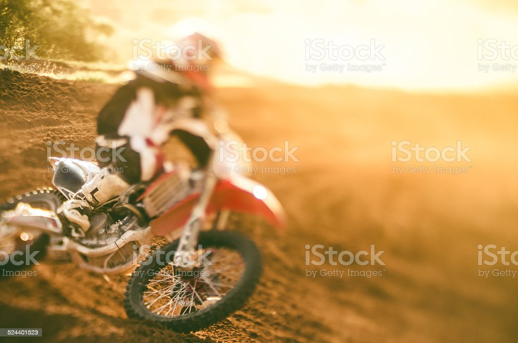 Motocross racer making a turn in dirt track stock photo