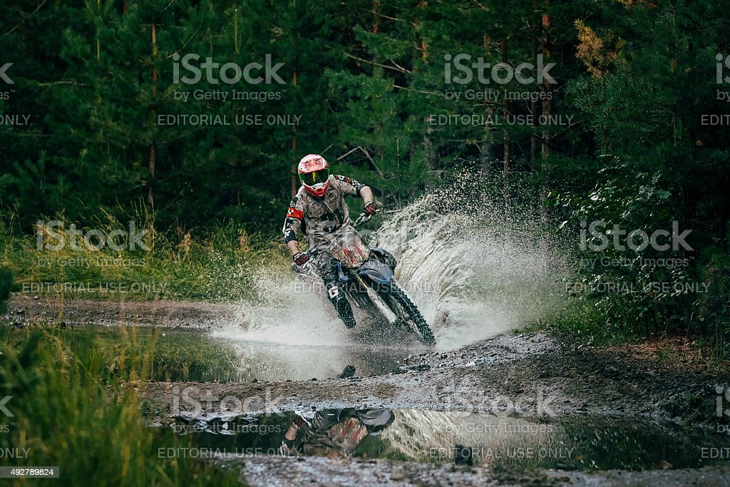 Motocross racer rides through a puddle stock photo