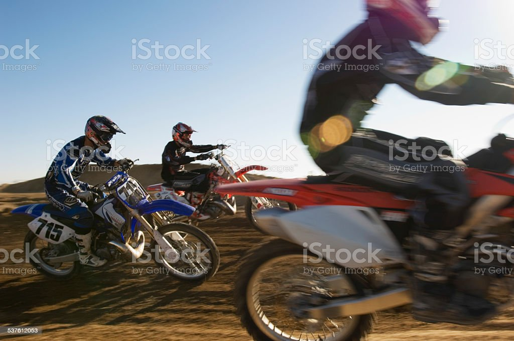 Motocross Racers Racing In Desert stock photo