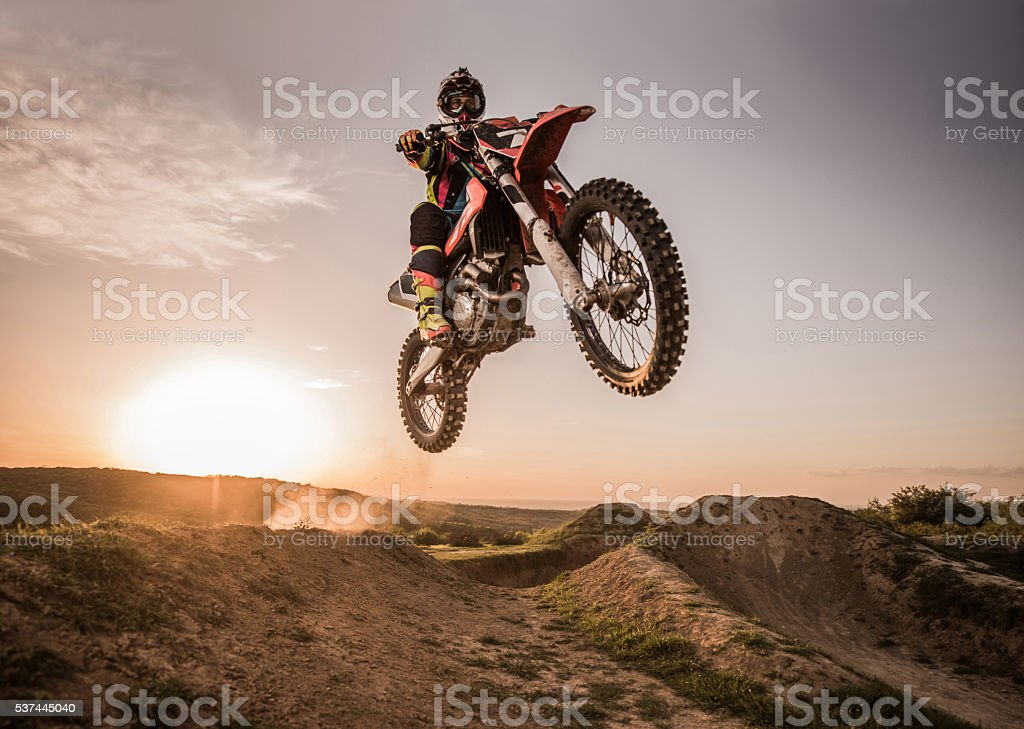 Motocross rider performing high jump at sunset. stock photo