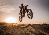 Motocross rider performing high jump at sunset.