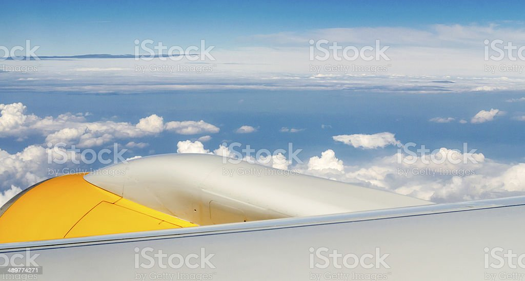 Motor and wing of an airplane flying above the clouds stock photo
