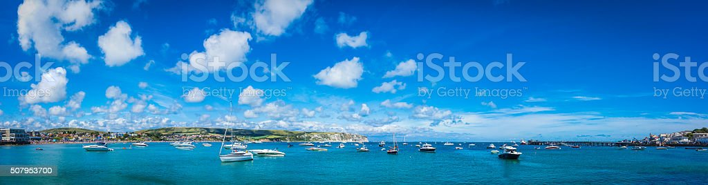 Motor boats and yachts moored in picturesque blue ocean harbour stock photo