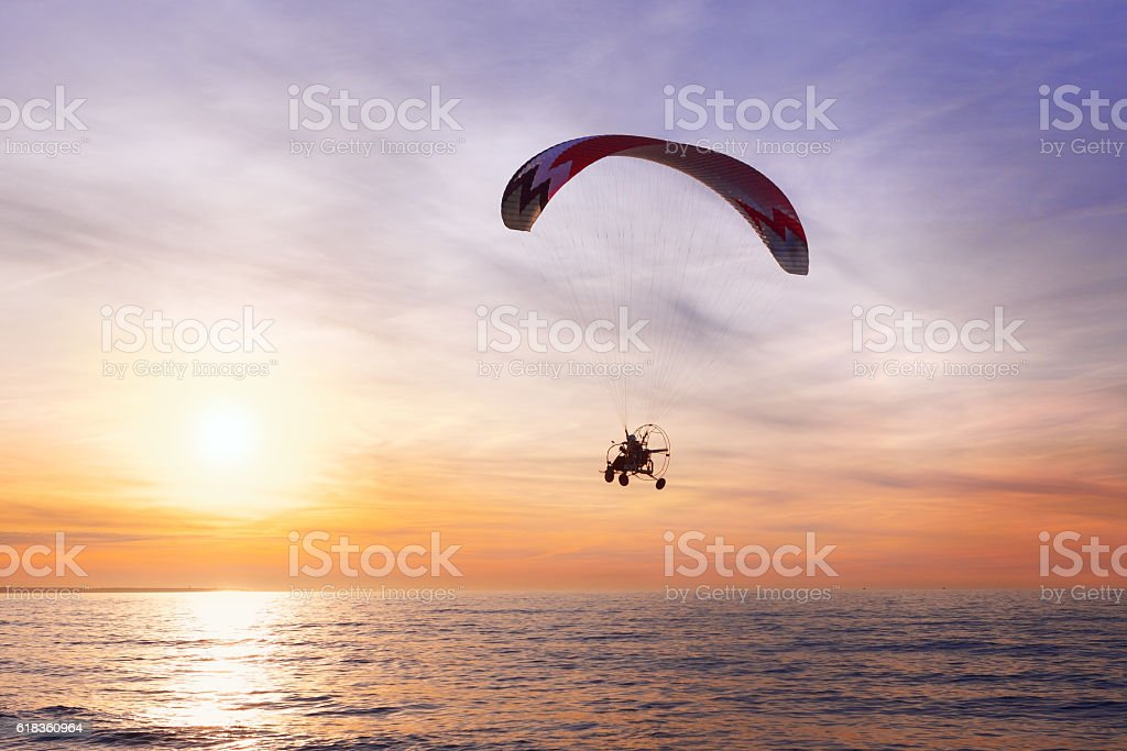Motor Glider flying over the sea during sunset stock photo