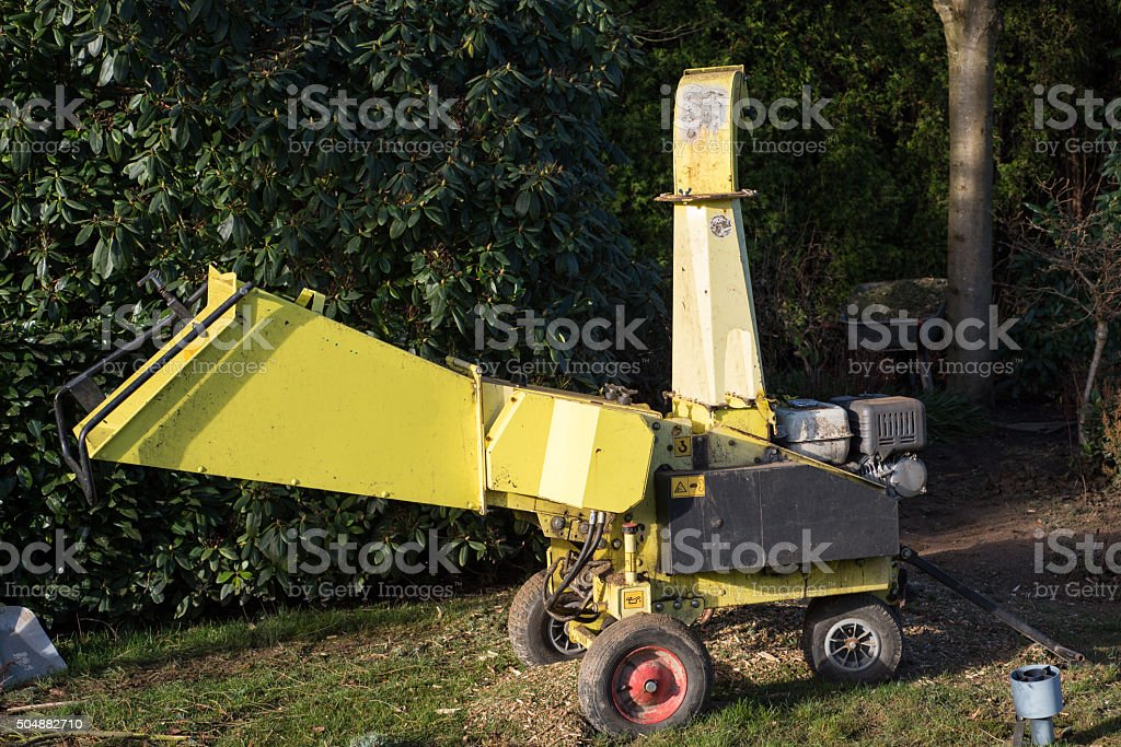 motor wood chipper standing in the park stock photo