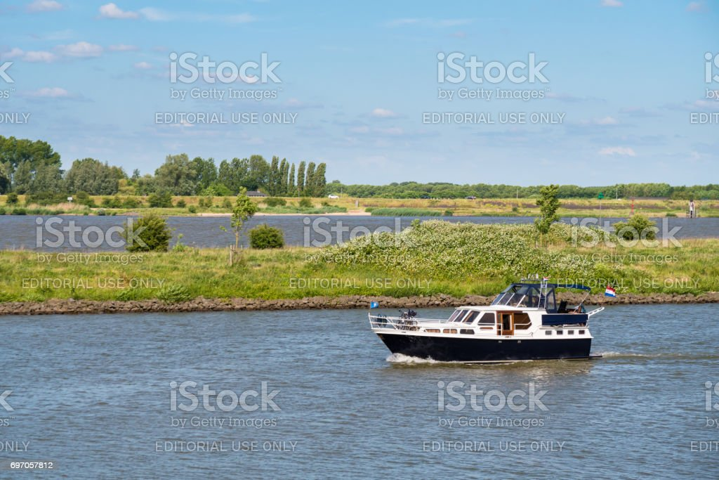 Motor yacht on river Afgedamde Maas near Woudrichem, Netherlands stock photo