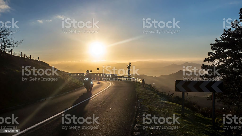 Motorbike riding at sunset stock photo