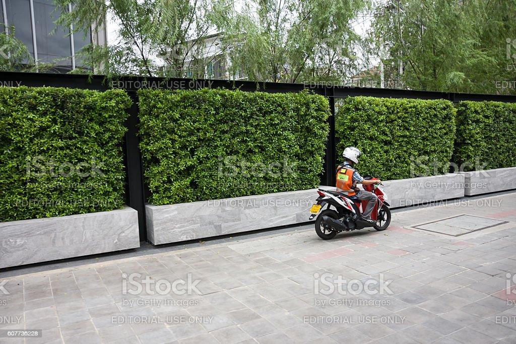 Motorbike taxi driving on sidewalk stock photo