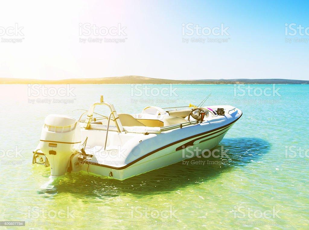 Motorboat moored in idyllic lagoon on sunny day stock photo