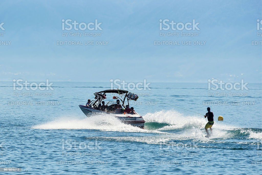 Motorboat with man wakeboarding in Lake Geneva in Lausanne stock photo