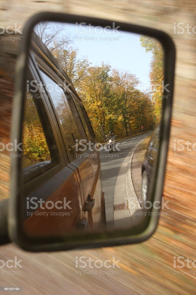 Motorciclist in the back mirror stock photo